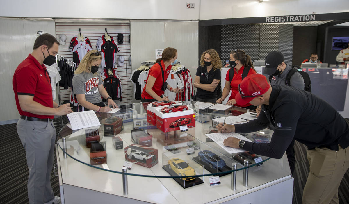 UNLV coaches fill out paperwork as they bring their Rebel Caravan to Dream Racing at the Las Ve ...