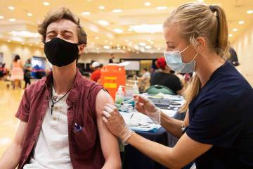Jared Fessler, left, gets his COVID-19 vaccination from Touro University Nevada physician assis ...