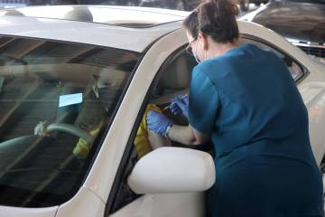 Teresa Woods gives a shot to Pamela Christensen of Henderson during a drive-thru COVID-19 vacci ...