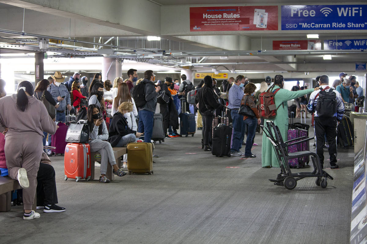 A crowd of people waits for ride shares at McCarran International Airport on Friday, March 19, ...