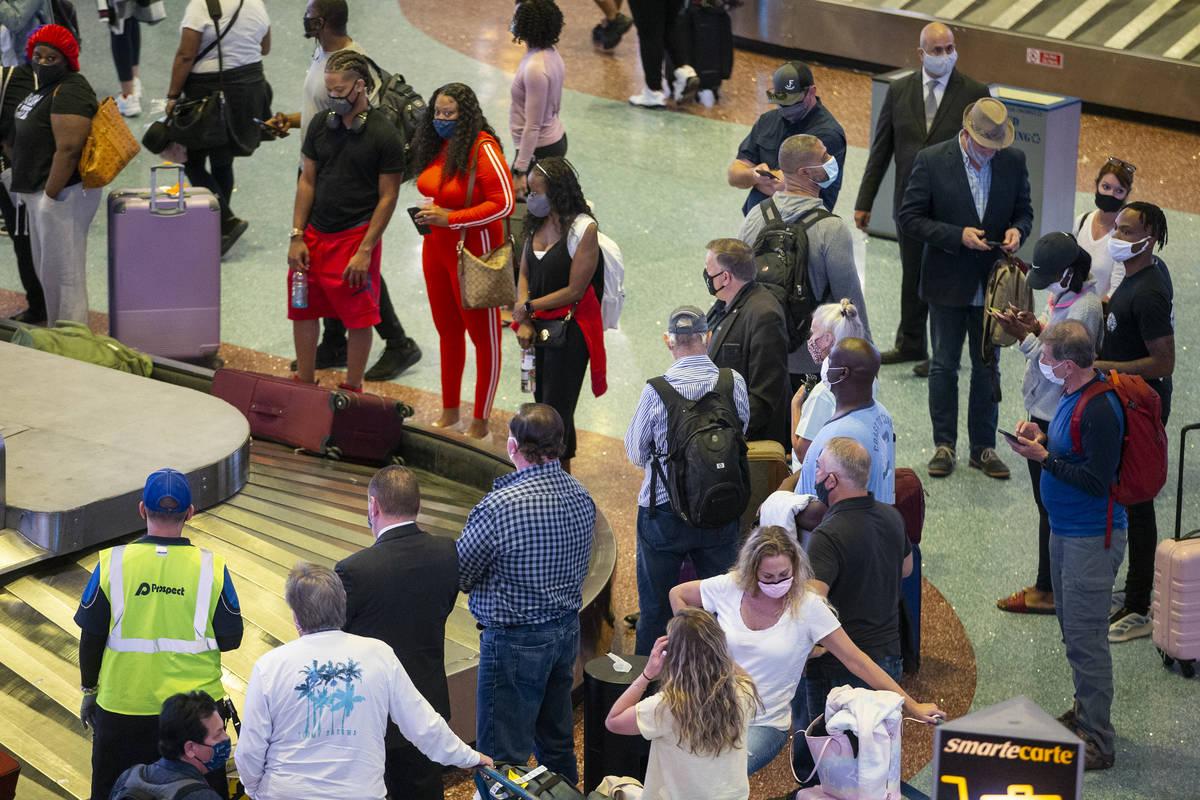 Travelers wait for their luggage at McCarran International Airport Terminal 1 in Las Vegas, Thu ...