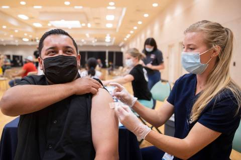 Jose Padilla, left, get's his COVID-19 vaccination from Touro University Nevada physician assis ...