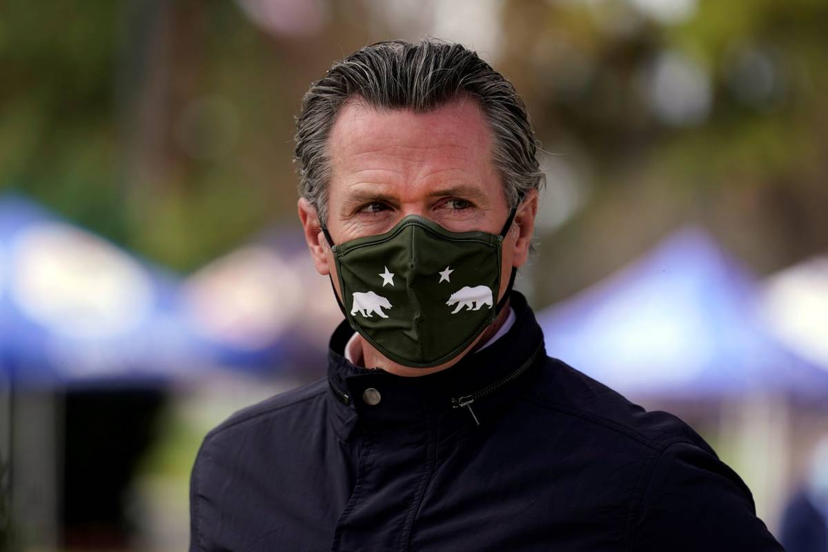 California Gov. Gavin Newsom wears a mask during a visit to a vaccination center in South Gate, ...