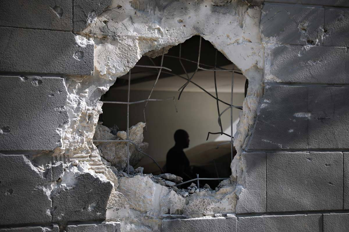 A man is seen trough a hole in a wall of a residential building after it was struck by a rocket ...