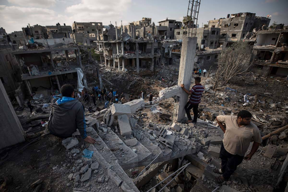 Palestinians inspect their destroyed houses following overnight Israeli airstrikes in town of B ...