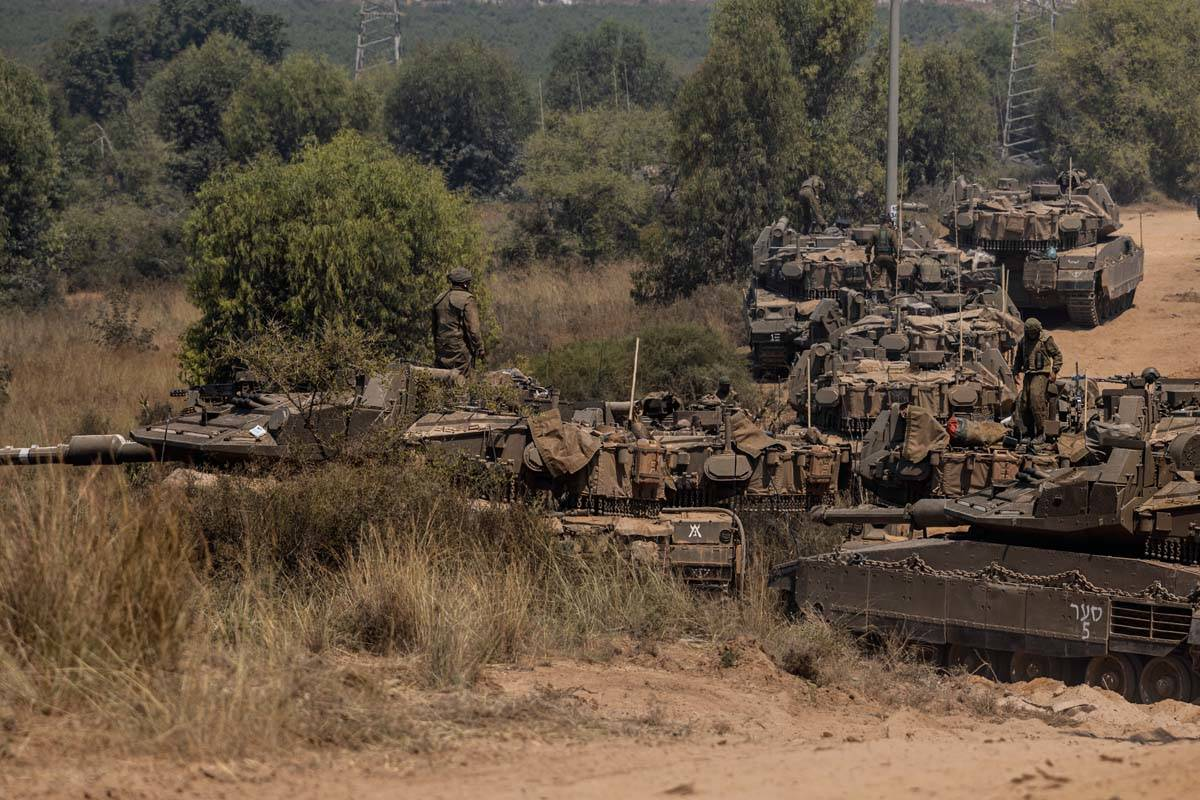 Israeli soldiers with armored vehicles gather in a staging ground near the border with Gaza Str ...