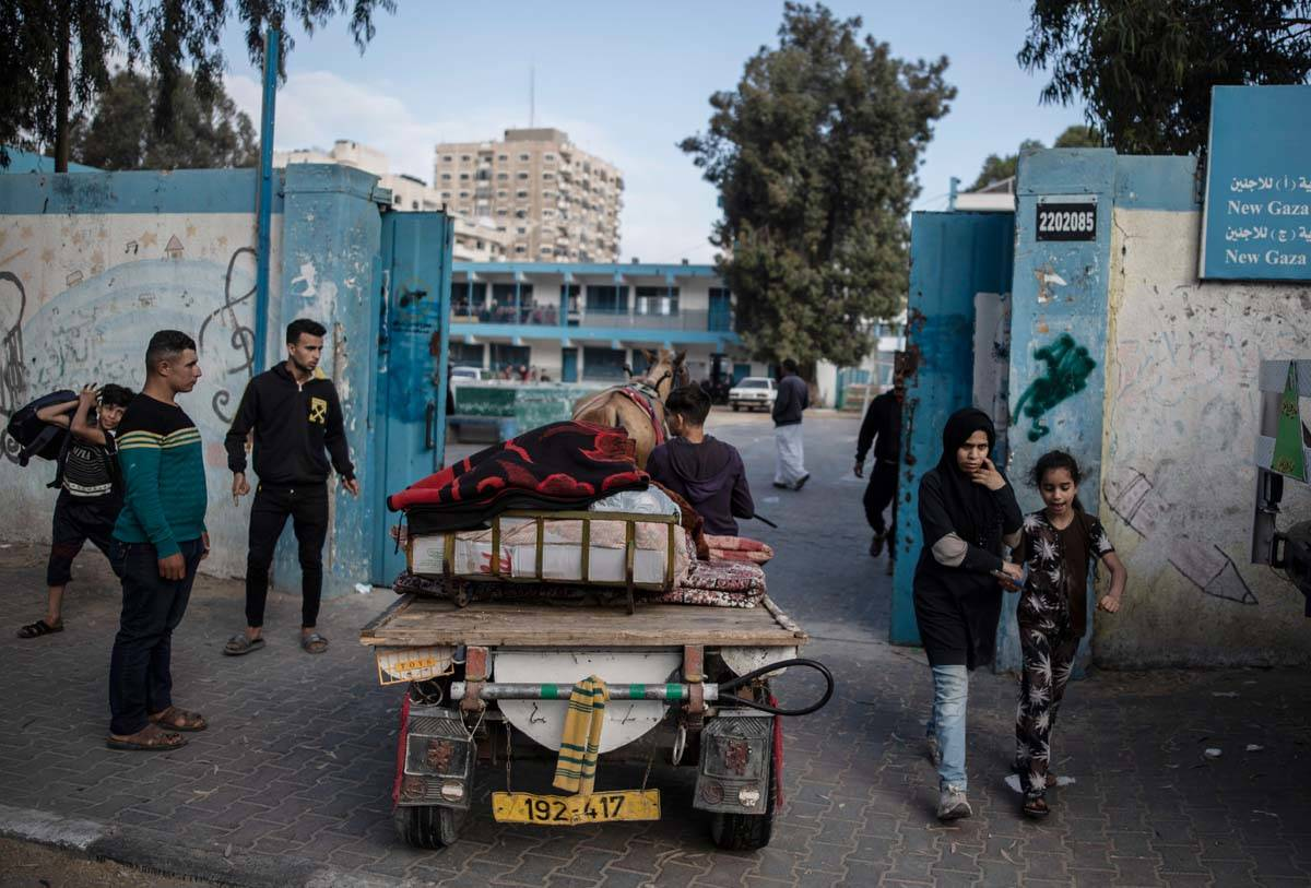 Palestinians flee their homes to a U.N. school after overnight Israeli heavy missile strikes on ...