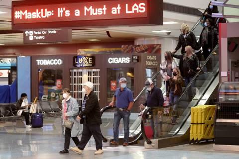 Masked travelers walk through Terminal 1 at McCarran International Airport in Las Vegas Friday, ...