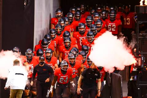 UNLV Rebels players run onto the field before taking on the Wyoming Cowboys in a football game ...