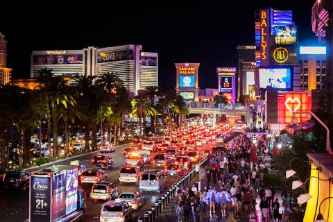 FILE - In this March 19, 2021, file photo, vehicles and crowds move along the strip in Las Vega ...
