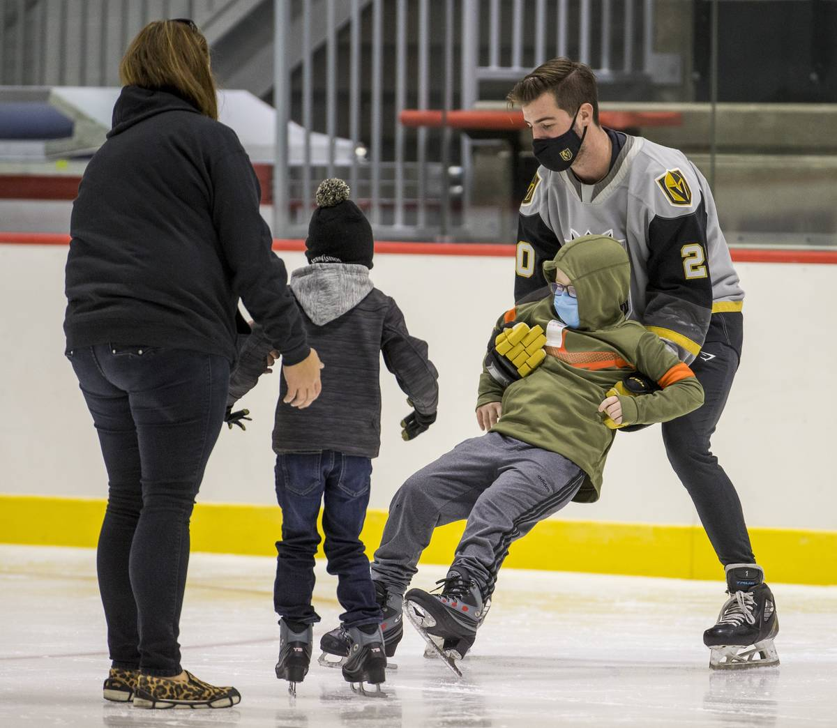 New Vegas Golden Knights goaltender Logan Thompson, right, helps a youngster with the Battle Bo ...