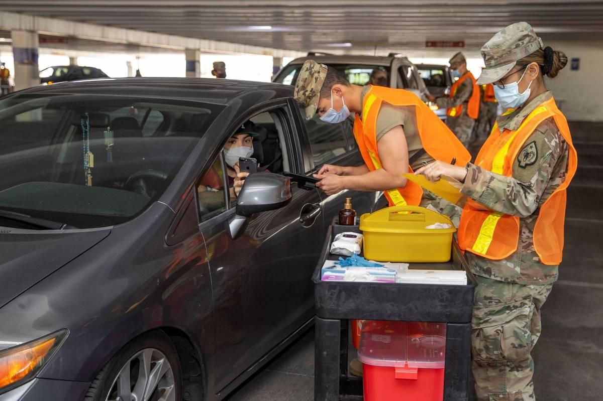 Andy Ruiz, left, looks on as Nevada National Guard SRA Dooley Gegen, center, gives him a shot d ...