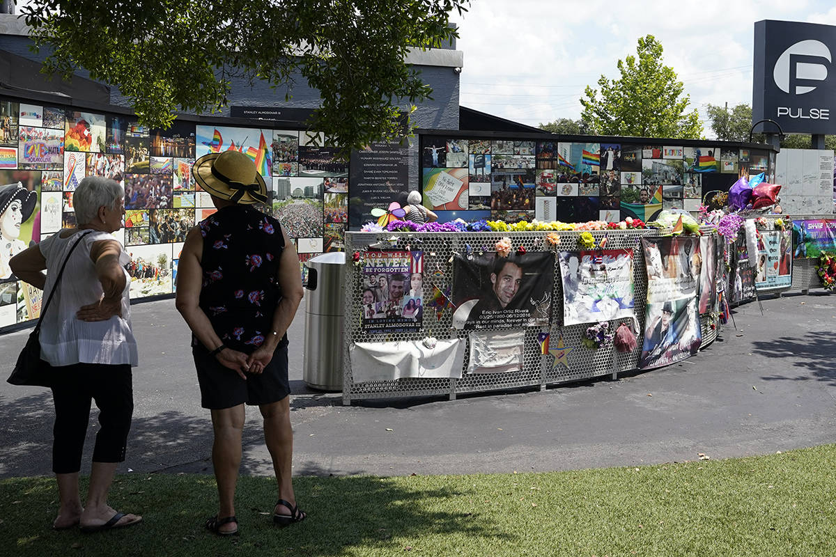 Visitors pay tribute to the display outside the Pulse nightclub memorial Friday, June 11, 2021, ...