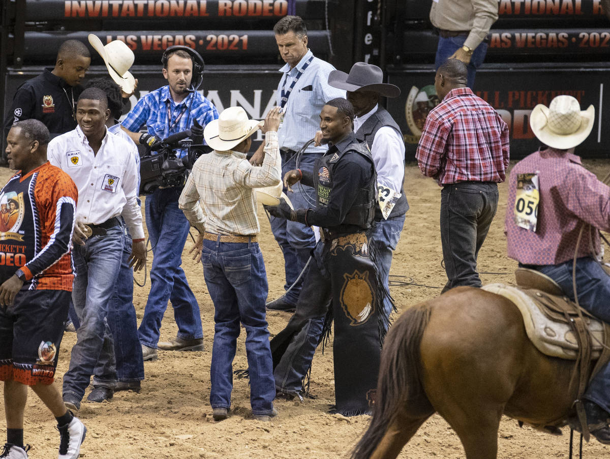 Winner of Bull Riding competition, Ouncie Mitchell, of Houston, Texas., center, congratulated ...