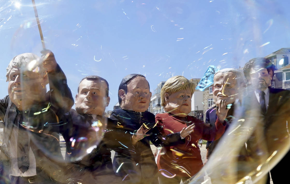 Protestors wear giant heads portraying the leaders of the G7 as they play with bubbles during a ...