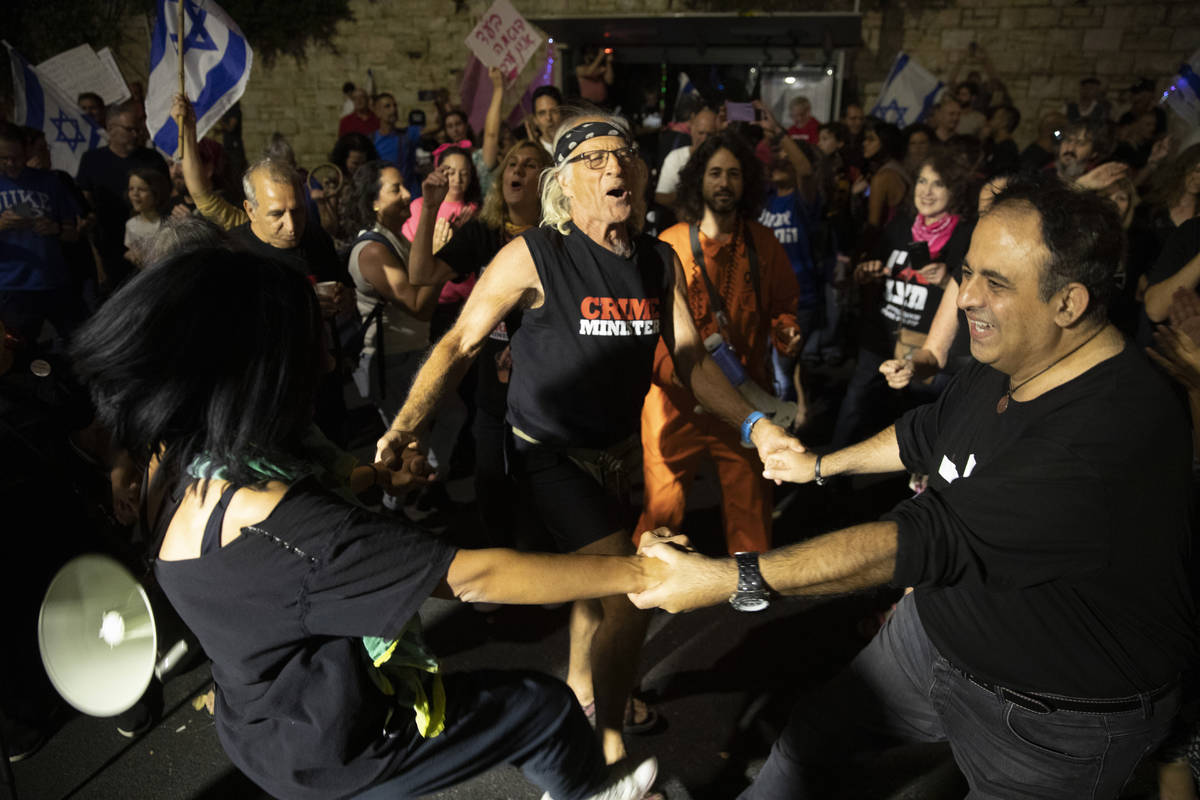Israeli protesters dance and cheer during a demonstration against Israeli Prime Minister Benjam ...