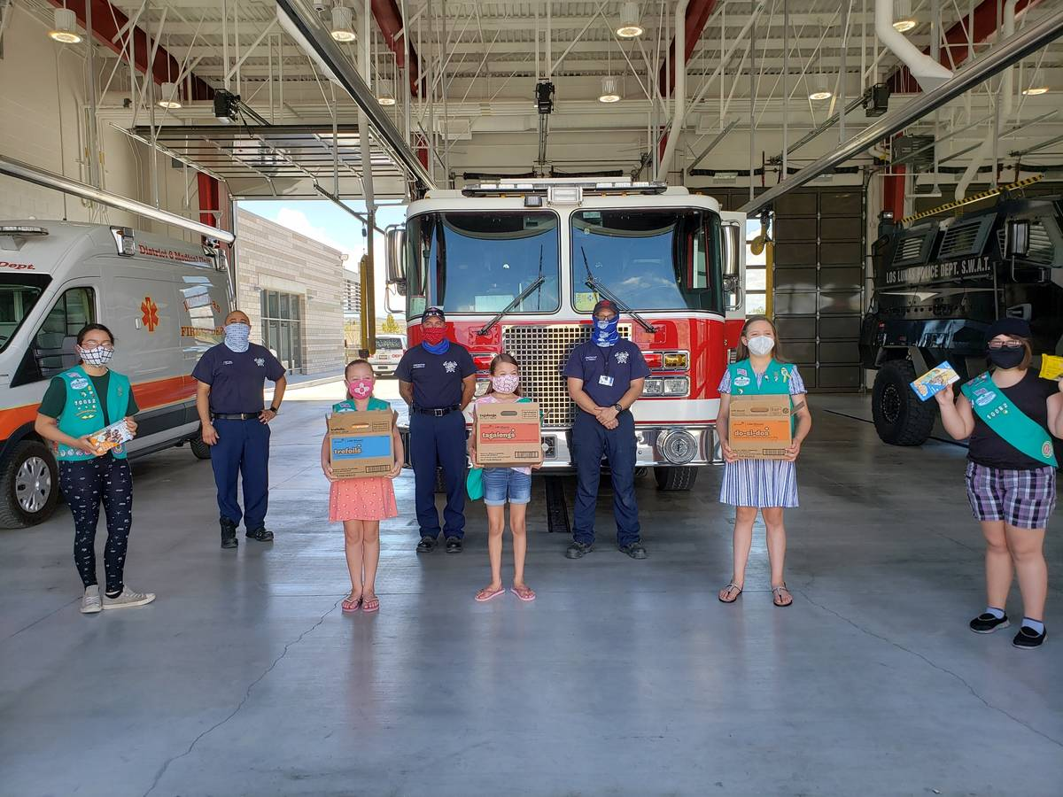 This undated photo provided by Girl Scouts of New Mexico Trails shows scouts donating cookies t ...