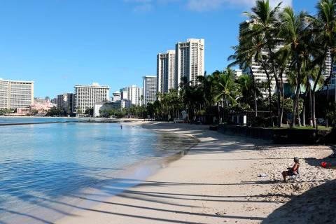 In this Oct. 2, 2020, file photo, a man sits on Waikiki Beach in Honolulu. (AP Photo/Caleb Jone ...