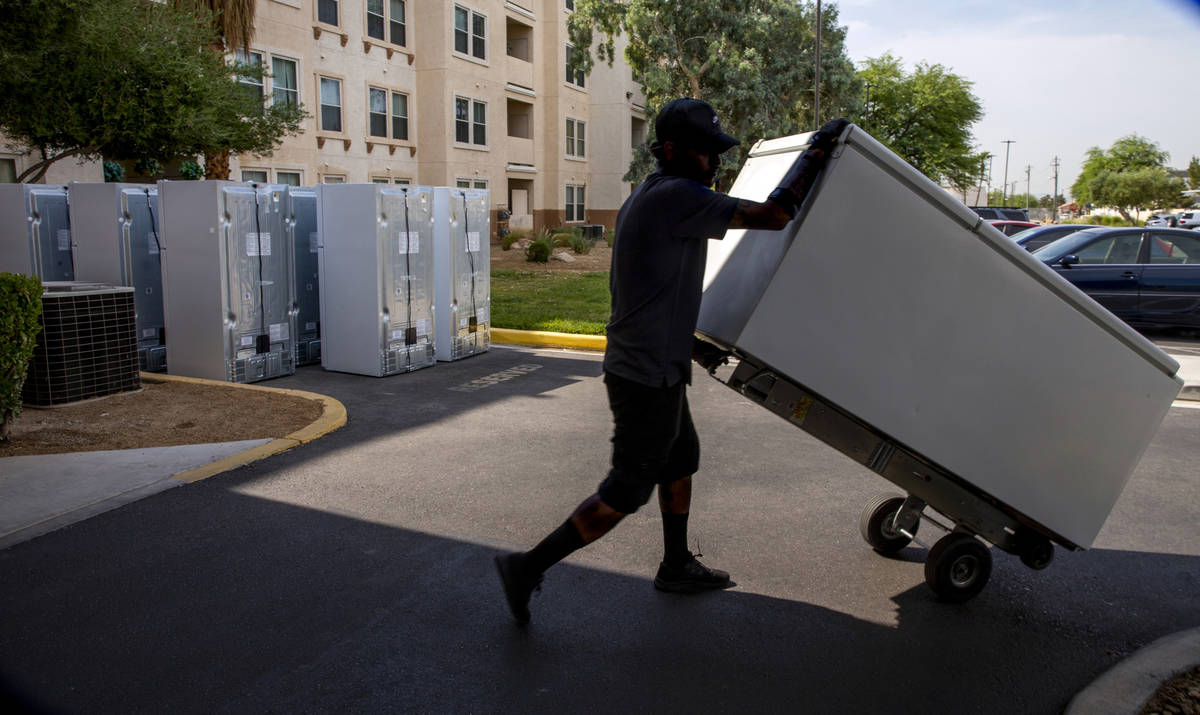 Lowe's employee Romanldo Lazaro moves one of the 98 fridges at Bonanza Pines Senior Living bein ...