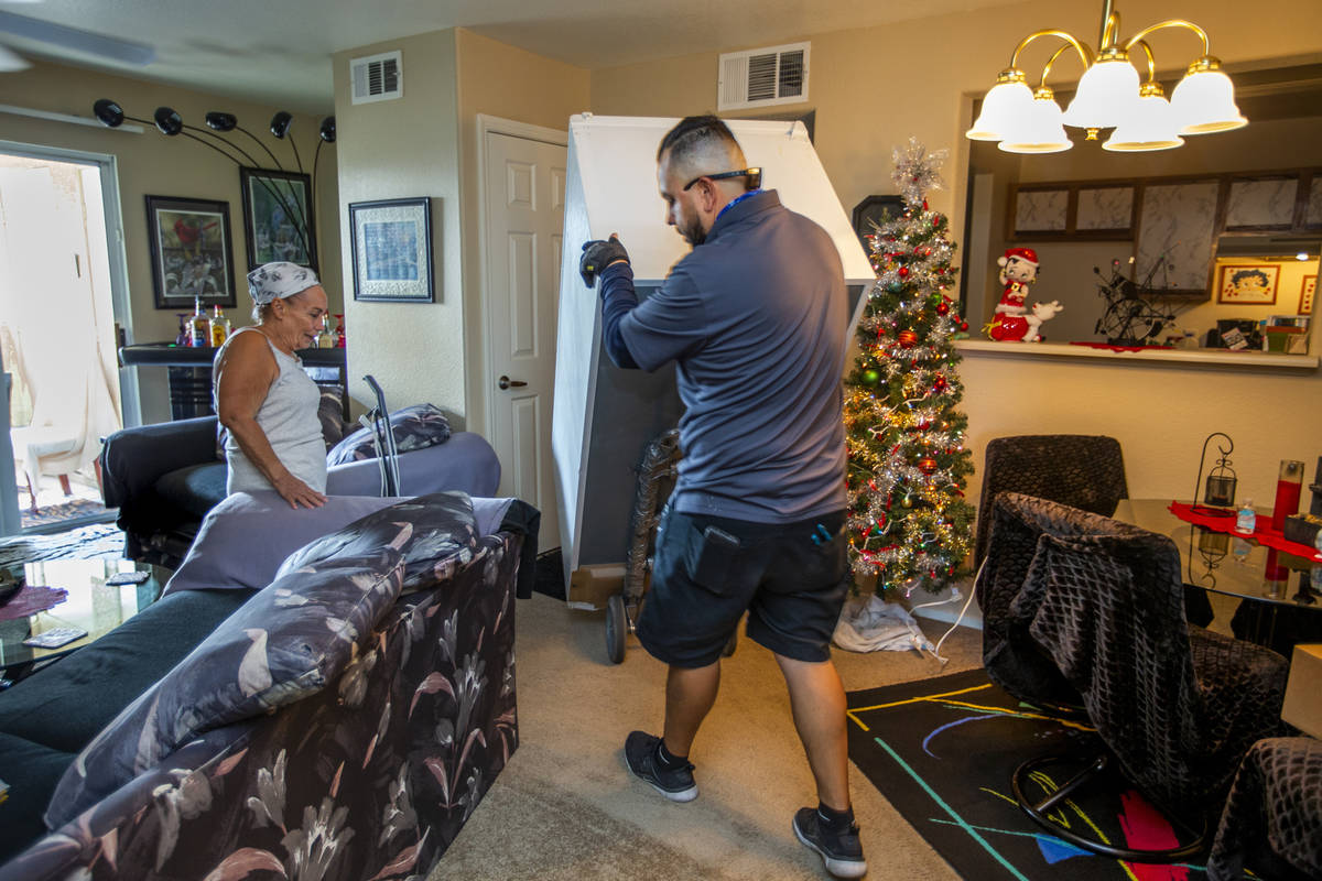 Resident Carol Sloncik, left, looks on as Lowe's employee Albert Vazquez delivers one of the 98 ...