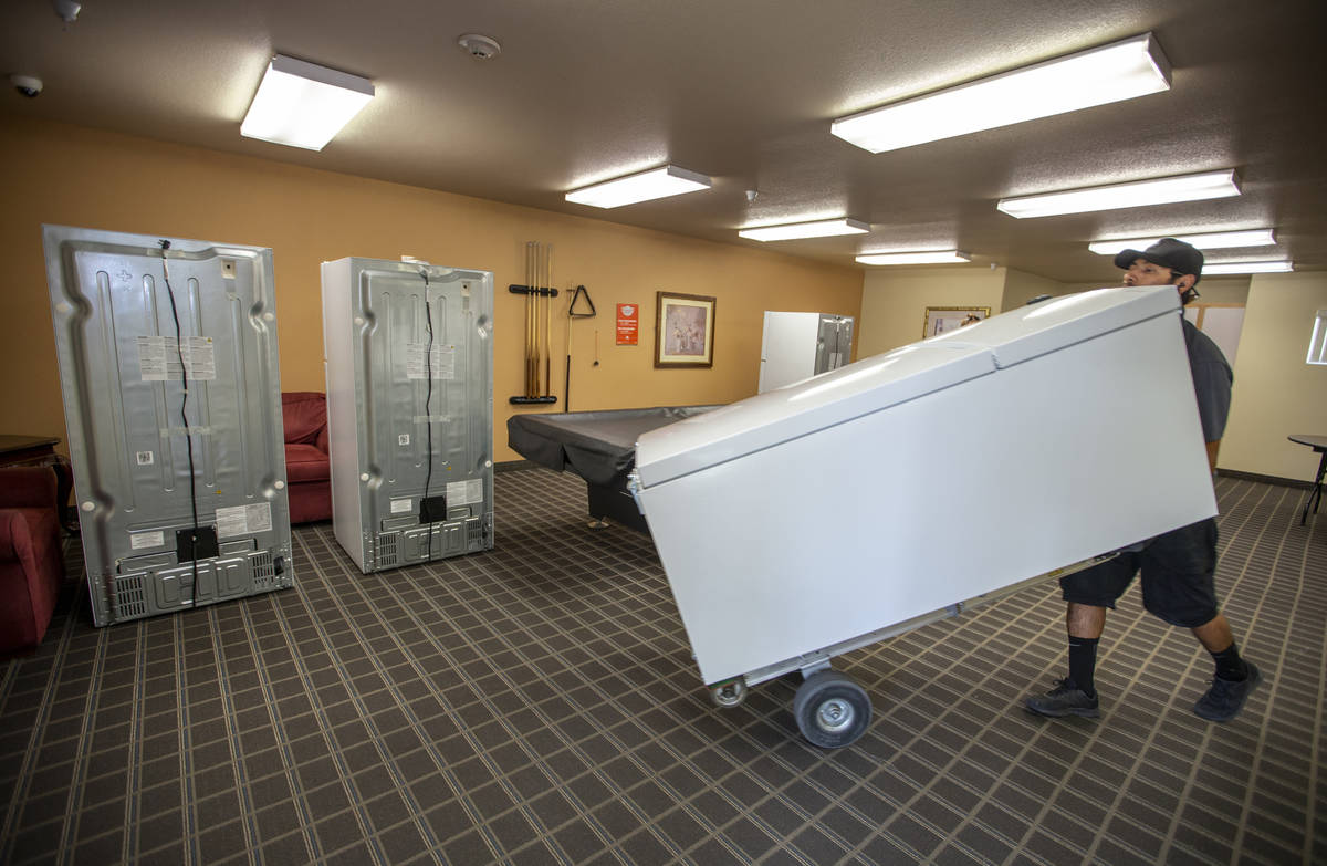 Lowe's employee Romanldo Lazaro moves in one of the 98 new fridges at Bonanza Pines Senior Livi ...
