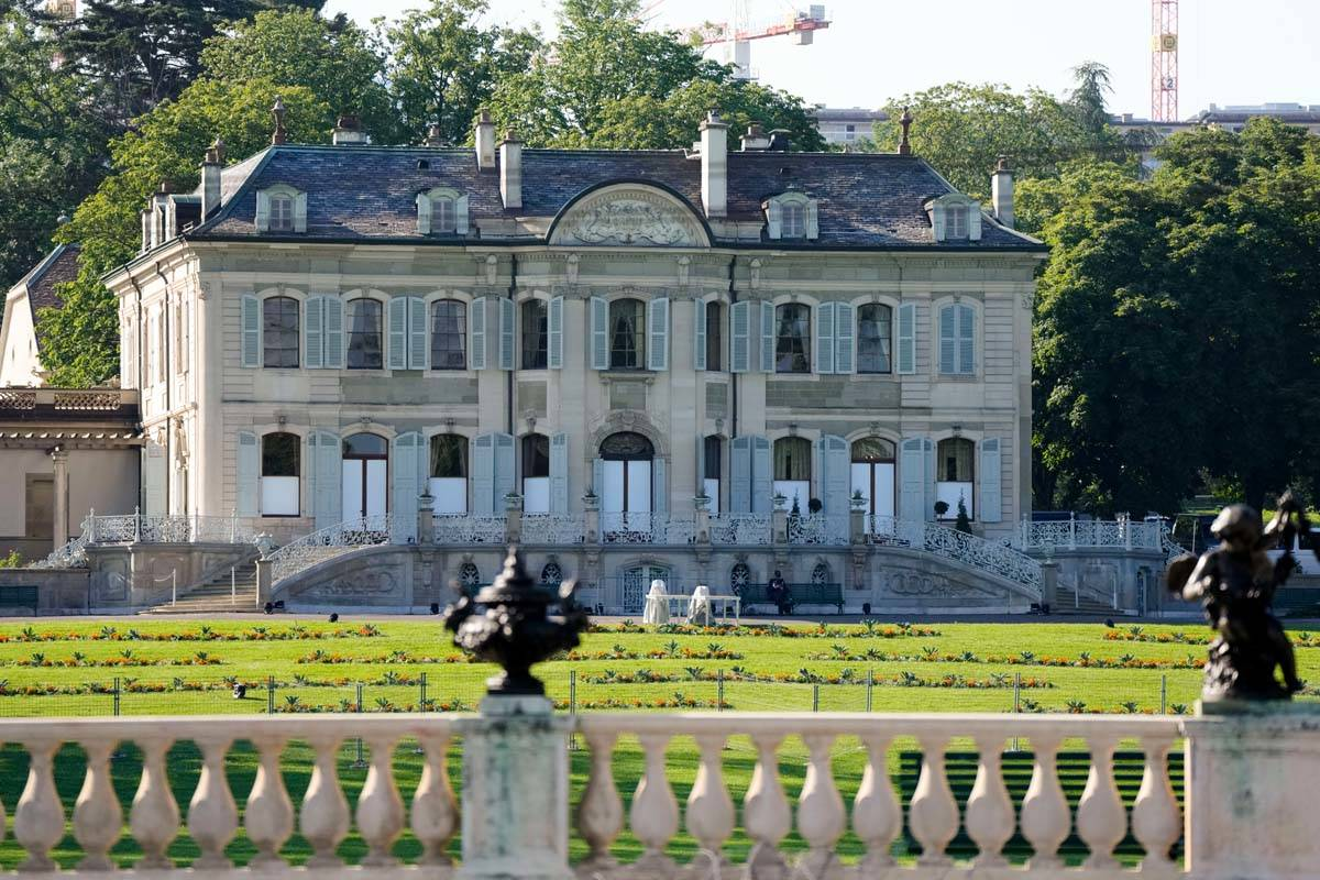 A police officer sits on a bench in in front of the 'Villa la Grange' ahead of the meeting of U ...