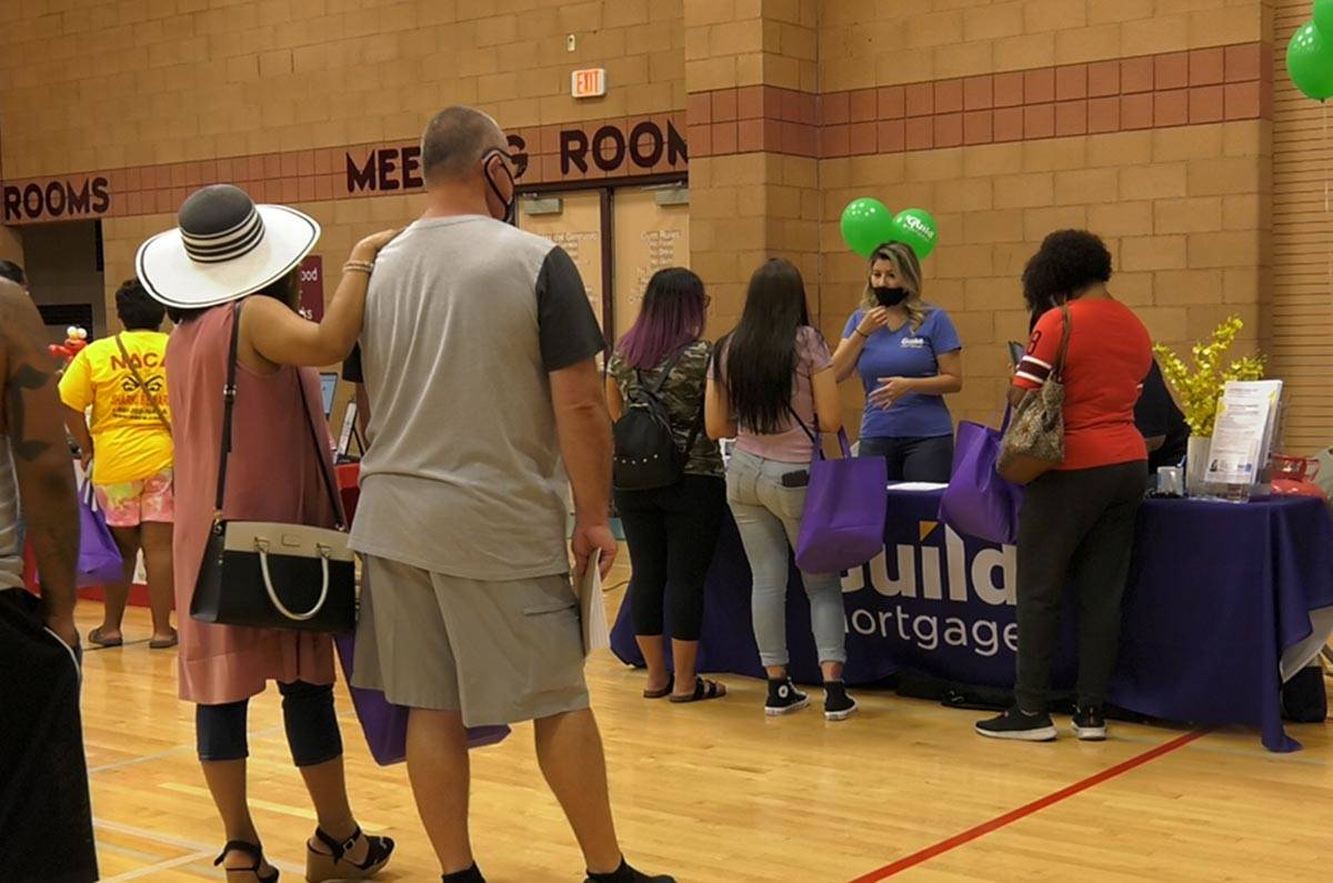 Prospective homebuyers wait in line to talk with a mortgage advisor from Guild Mortgage Saturda ...