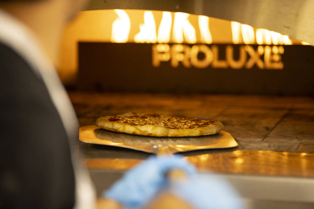 A pizza is taken out of the oven at the Fly Pie pizza drive-thru at the intersection of St. Ros ...
