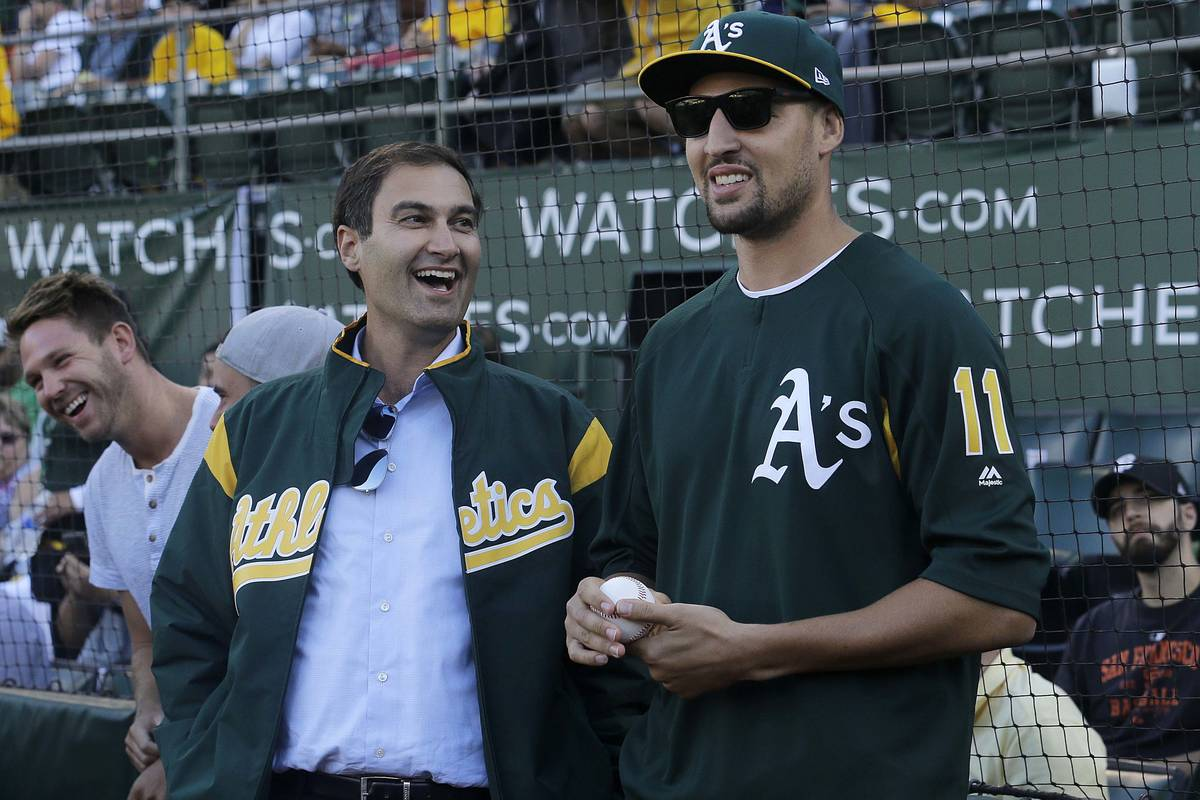 Oakland Athletics president Dave Kaval, left, laughs with Golden State Warriors basketball play ...