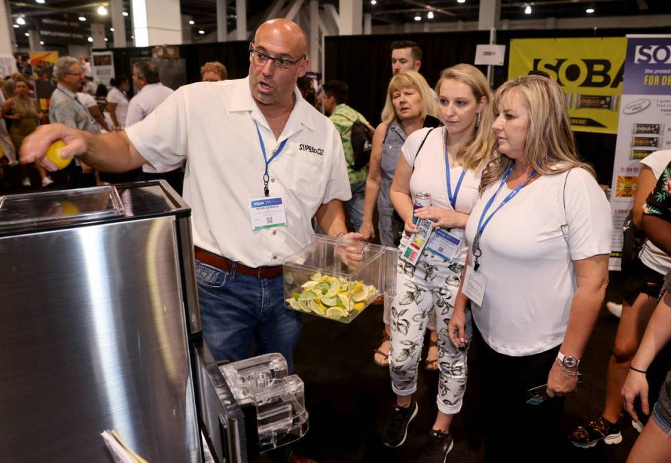 Kevin Szakacs of Las Vegas demonstrates his automatic slicer to Janine Andrews, right, and Kait ...