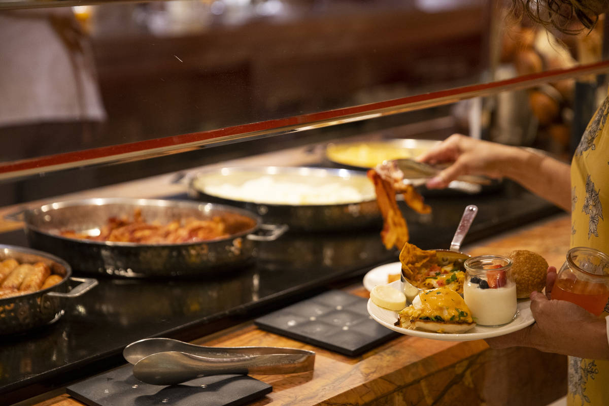 A person serves their own food at The Buffet at Wynn Las Vegas, Wednesday, June 30, 2021 in Las ...