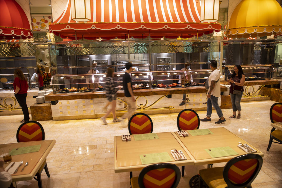 People walk past the food stations at The Buffet at Wynn Las Vegas, Wednesday, June 30, 2021 in ...
