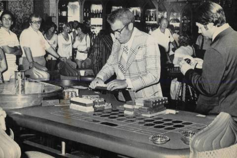 Agents count chips at a roulette wheel while Aladdin Hotel casino employees watch after state g ...