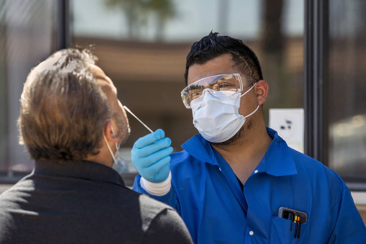 Practice Manager Jose Tirana conducts a COVID-19 test on a patient at Sahara West Urgent Care & ...