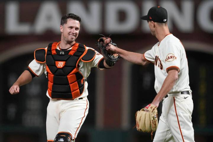 San Francisco Giants catcher Buster Posey, left, celebrates with pitcher Tyler Rogers after the ...