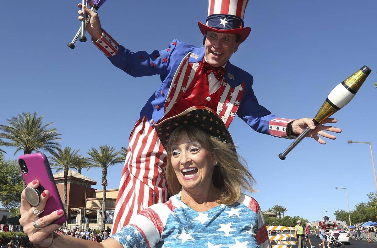 Kathy Koch takes a photo with a man dressed as Uncle Sam during the 25th annual Summerlin Counc ...