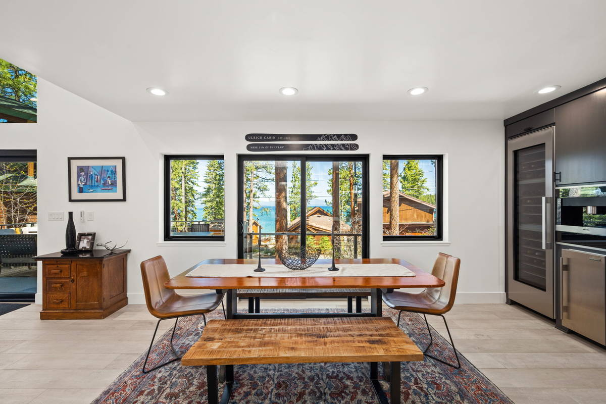 The dining room's expansive windows and slider allow natural light to flood the space. The un ...
