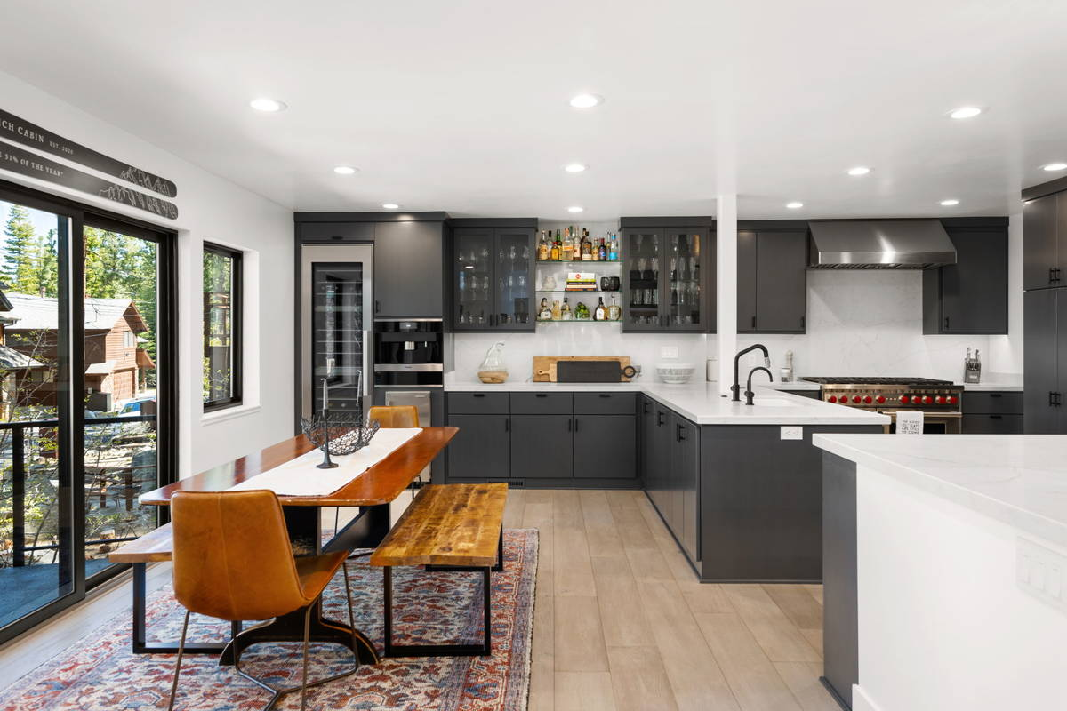 Striking white quartz counters contrast the dark gray custom cabinetry in the chic kitchen. A l ...