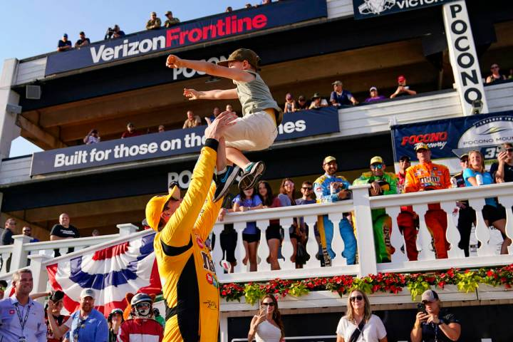 Kyle Busch, left, tosses his six-year-old son Brexton as he celebrates after winning a NASCAR C ...