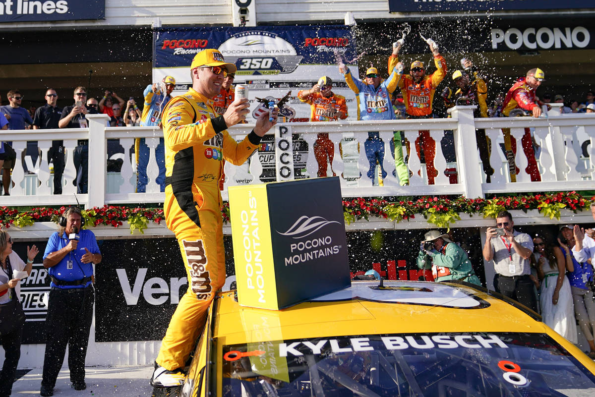 Kyle Busch celebrates with teammates after winning a NASCAR Cup Series auto race at Pocono Race ...