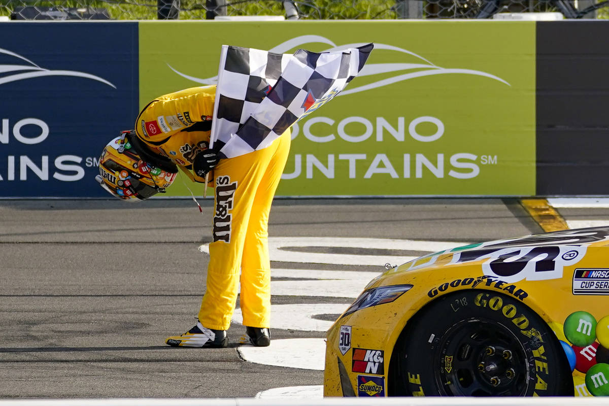 Kyle Busch takes a bow with the checker flag after winning a NASCAR Cup Series auto race at Poc ...
