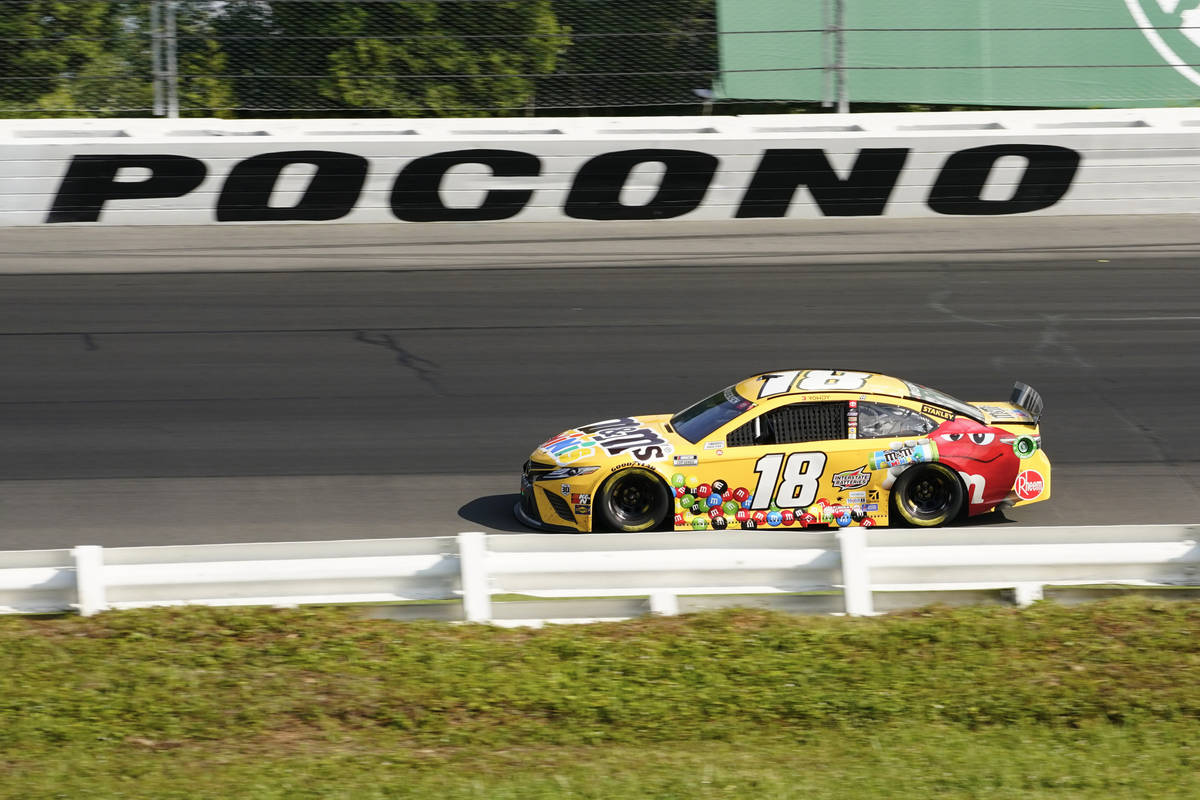 Kyle Busch (18) motors around the track during a NASCAR Cup Series auto race at Pocono Raceway, ...