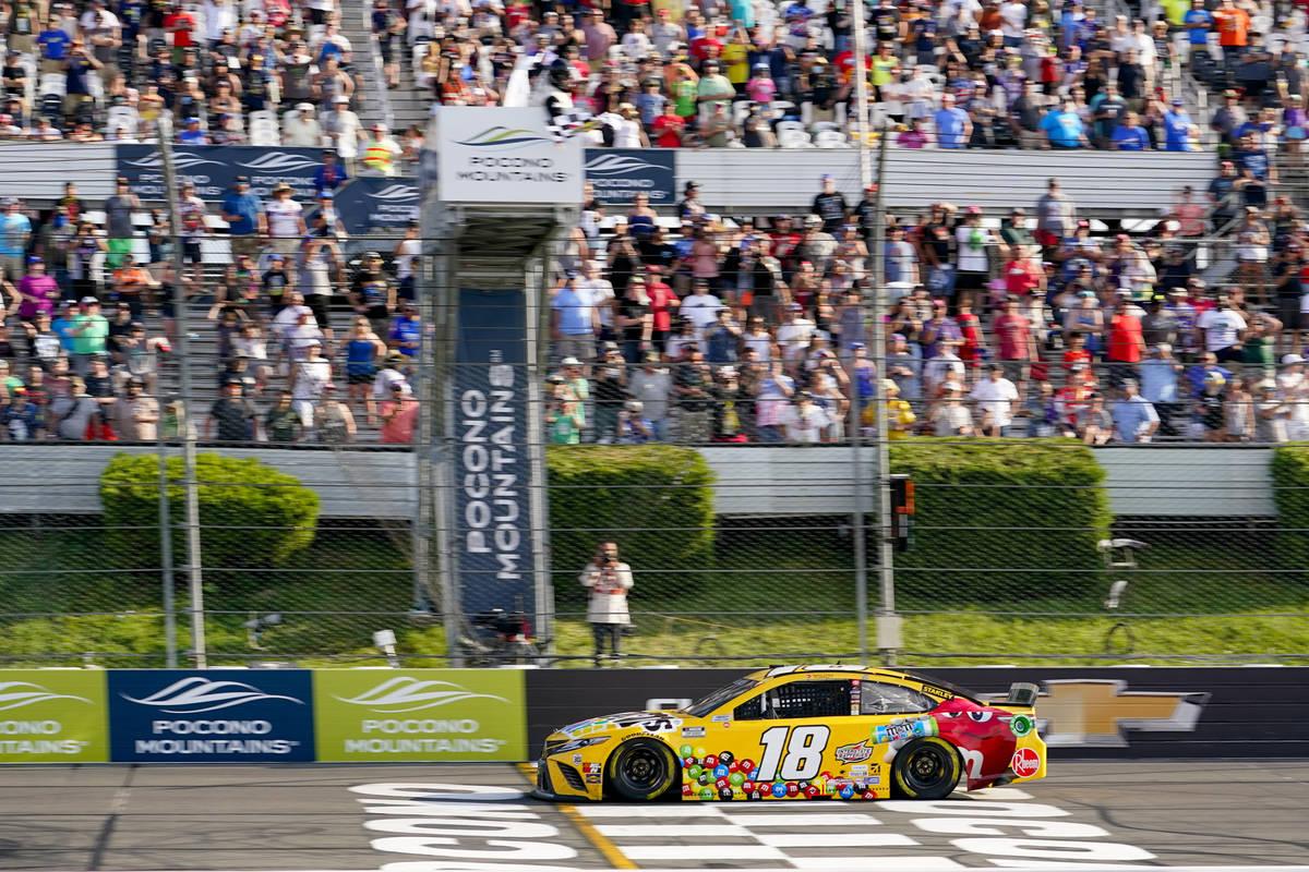 Kyle Busch (18) takes the checker flag to win the NASCAR Cup Series auto race at Pocono Raceway ...