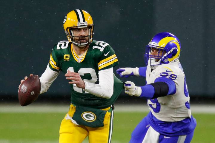 Green Bay Packers quarterback Aaron Rodgers (12) throws under pressure from Los Angeles Rams' A ...
