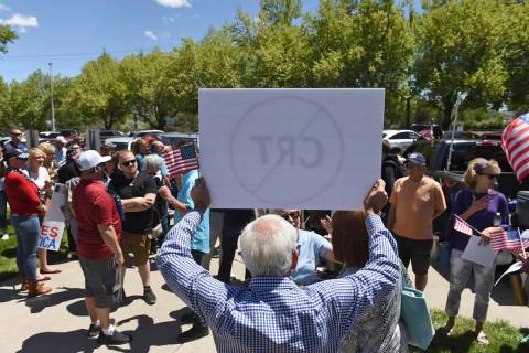 A man holds up a sign against Critical Race Theory during a protest outside a Washoe County Sch ...