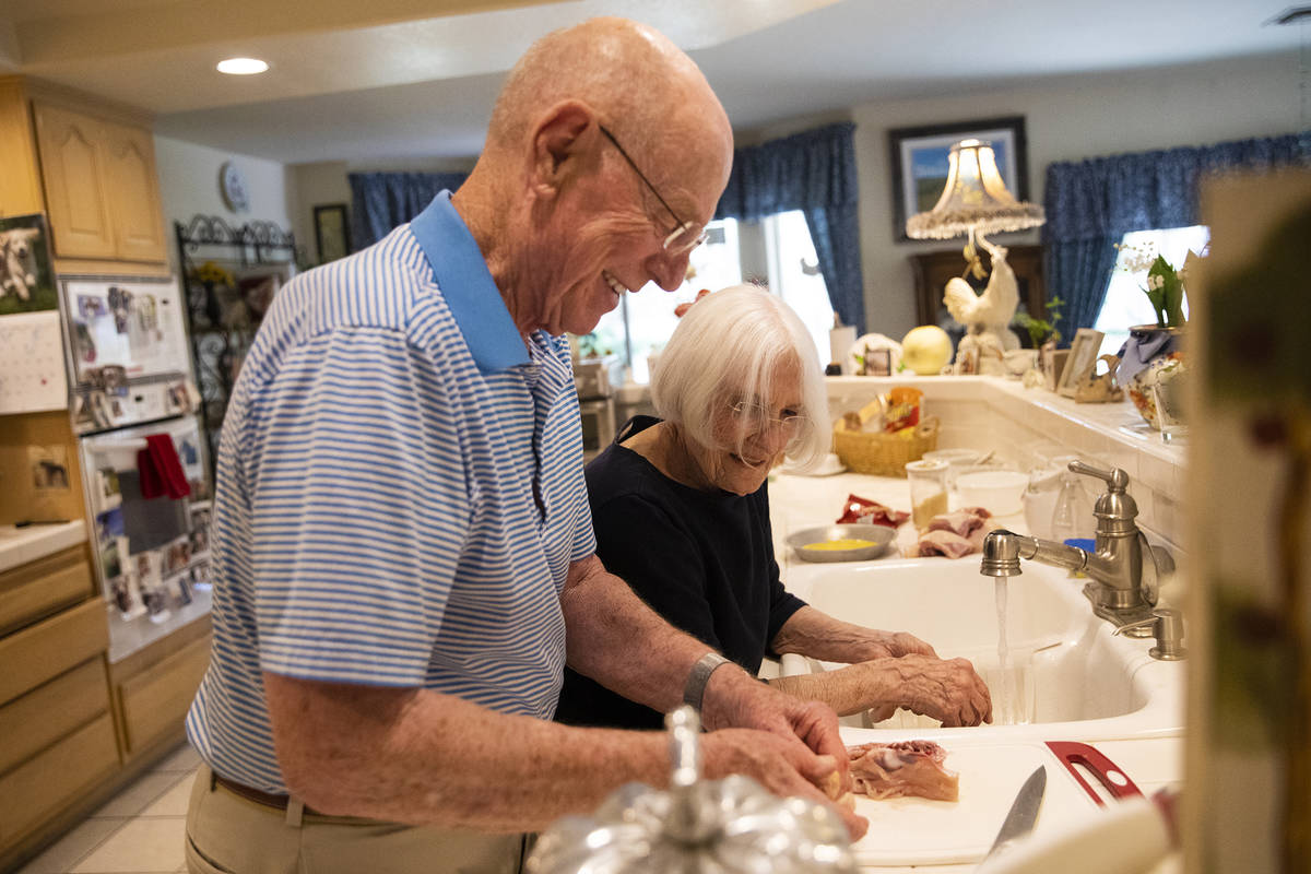 Gary Robinson helps his wife Judy Robinson cook dinner at their home in Las Vegas, Tuesday, Jun ...