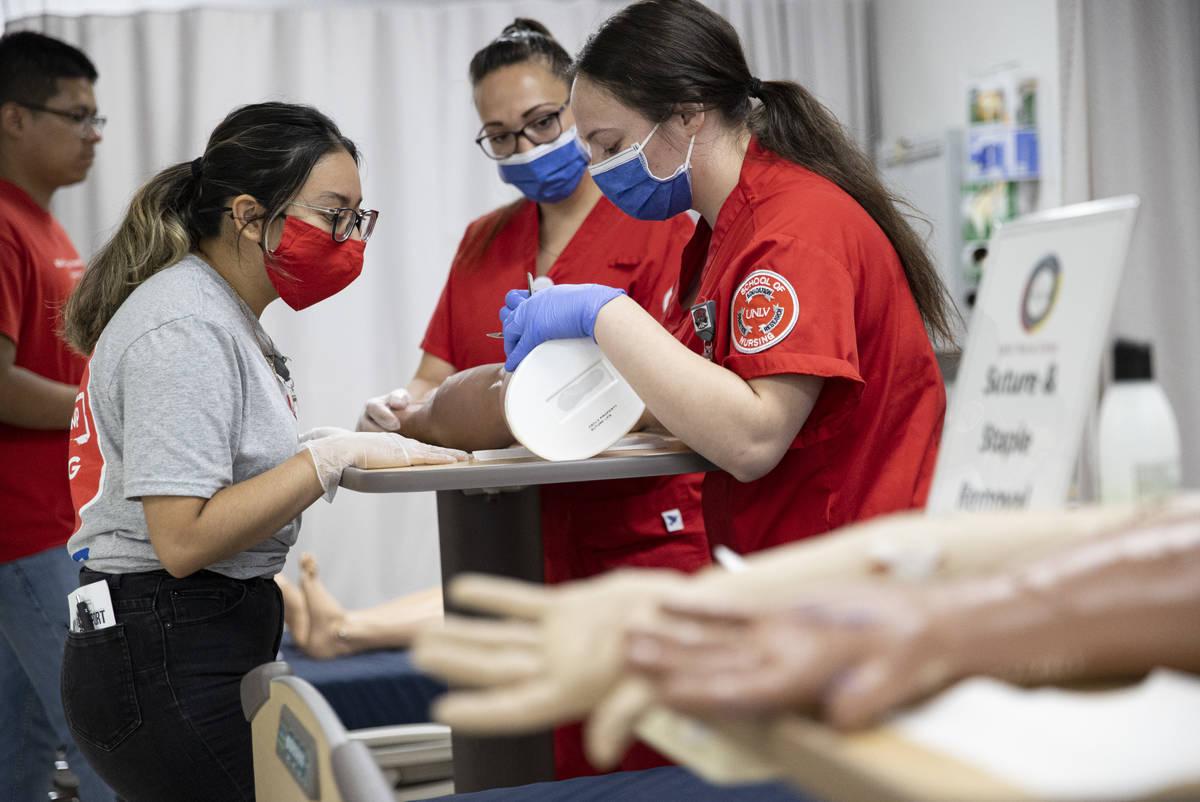 Northwest Career And Technical Academy student Natalie Sanchez, left, listens as UNLV nursing s ...