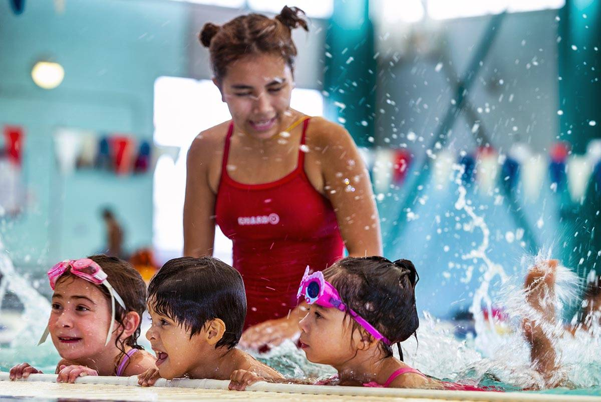 Lorelai Zimring, 5, Stefan Flores, 4, and Ariana Villeda, 4, practice their kicking for swim in ...