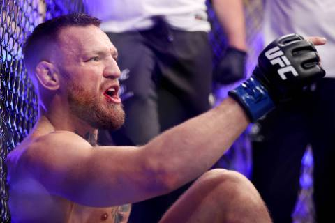 Conor McGregor yells after hurting his foot in the first round of a lightweight bout against Du ...