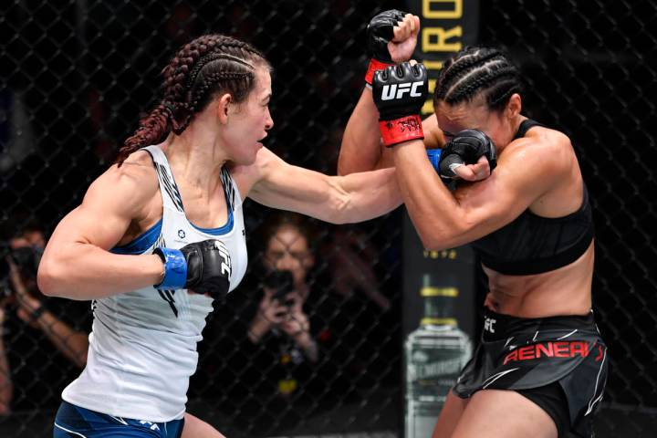 Miesha Tate punches Marion Reneau in their bantamweight bout during the UFC Fight Night event a ...